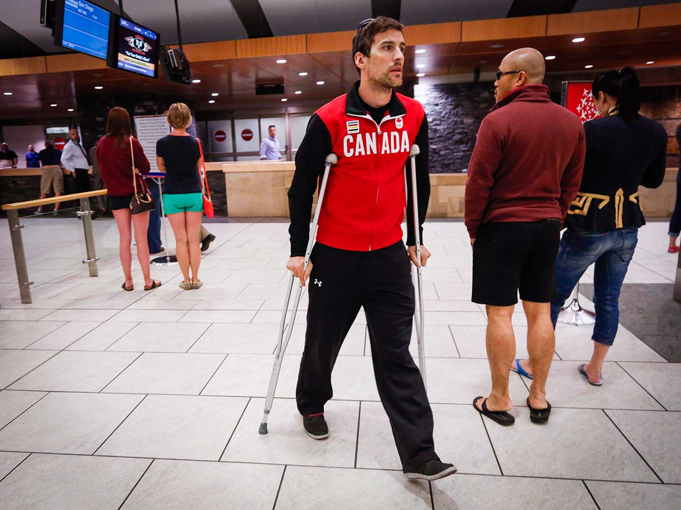 Denny Morrison walks on crutches on May 25th at the Calgary International Airport.