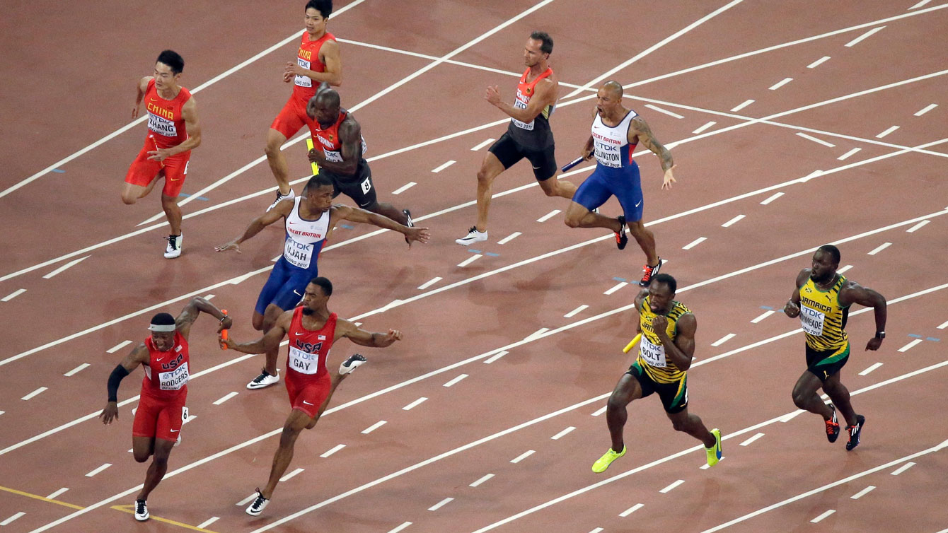 Mike Rodgers (bottom left, in red) receives the baton past the exchange zone from Tyson Gay of USA in the men's 4x100m final at the IAAF World Championships in Athletics on August 29, 2015.