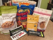 Assorted snacks, including dried mangos, dried apple, quinoa granola for breakfast, almonds, protein bars.