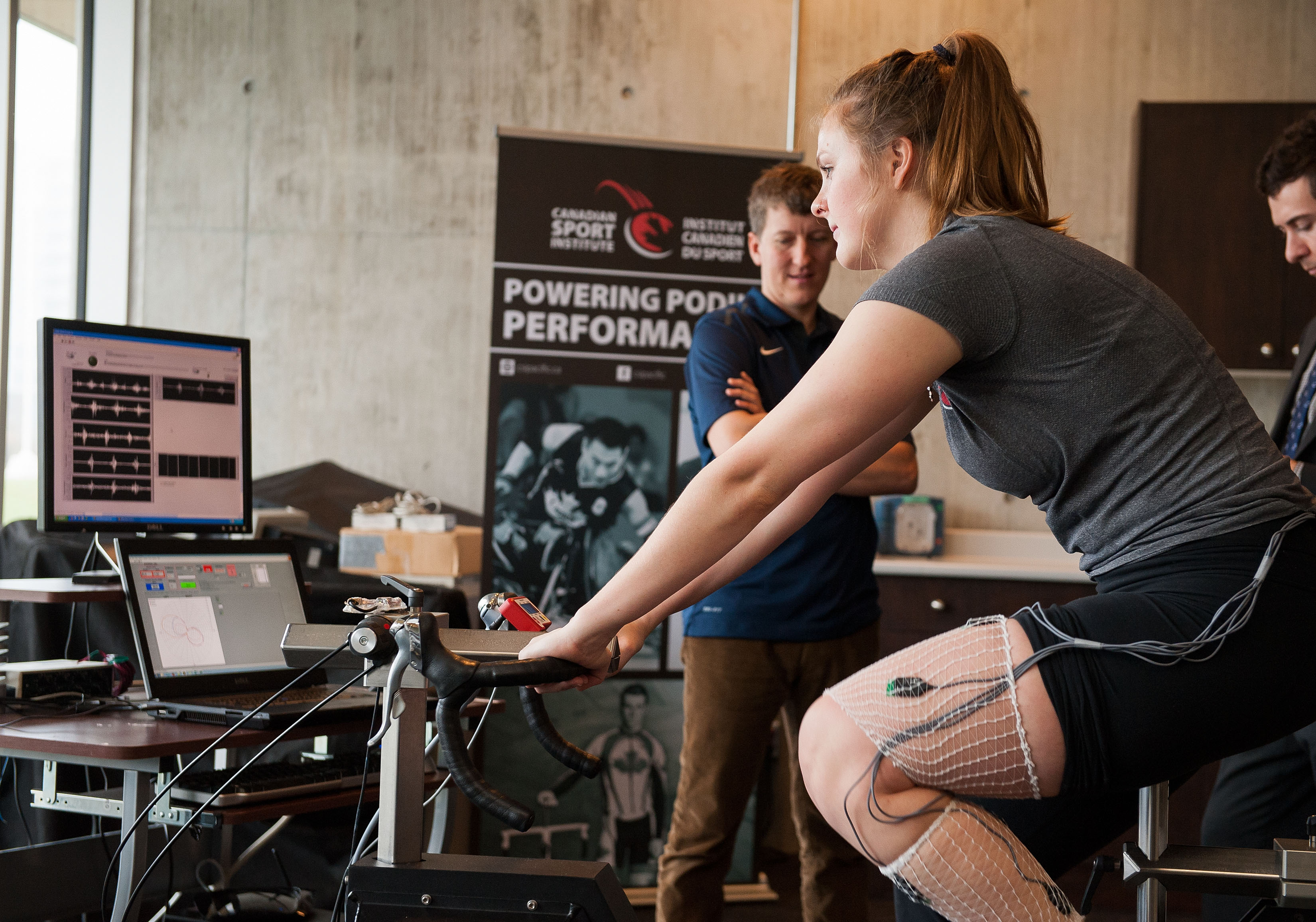 Researcher Matt Jesnen of the Canadian Olympic and Paralympic Sport Institute Network, watches colleague Monica McKeown demonstrate the first bike to measure the neuromechanical (NM) and physiological measurement techniques of high performance athletes at their lab on January 7, 2015.