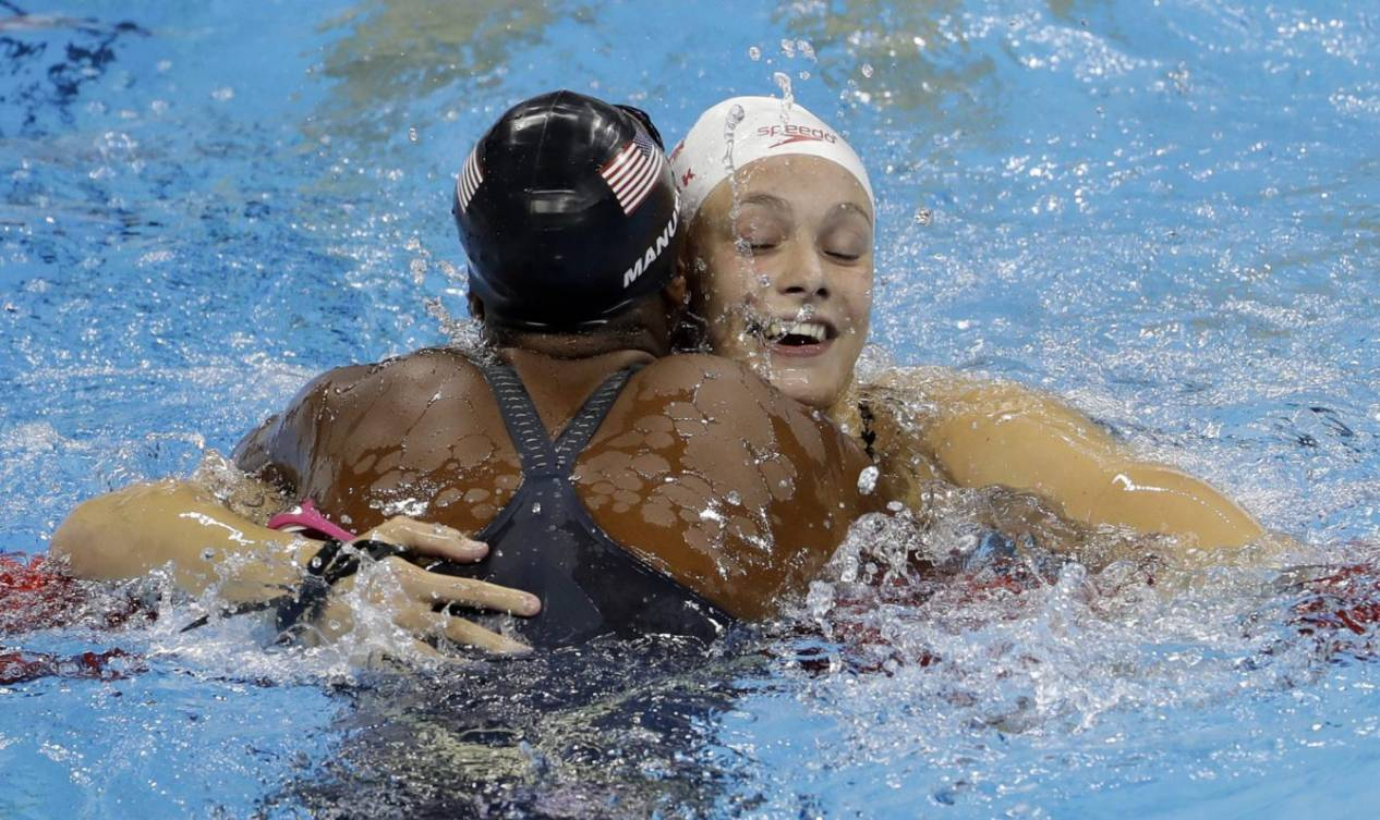 United States' Simone Manuel, left, and Canada's Penny Oleksiak celebrate winning joint gold and setting a new olympic record in the women's 100-meter freestyle during the swimming competitions at the 2016 Summer Olympics, Thursday, Aug. 11, 2016, in Rio de Janeiro, Brazil. (AP Photo/Natacha Pisarenko)