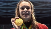 Canada's Penny Oleksiak holds up her gold medal after her first-place finish in the women's 100m freestyle finals during the 2016 Olympic Summer Games in Rio de Janeiro, Brazil, on Friday, Aug. 12, 2016. THE CANADIAN PRESS/Sean Kilpatrick