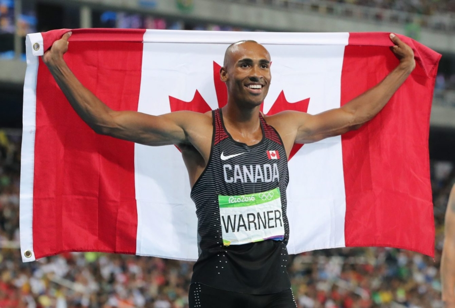 Damian Warner holds a Canadian flag