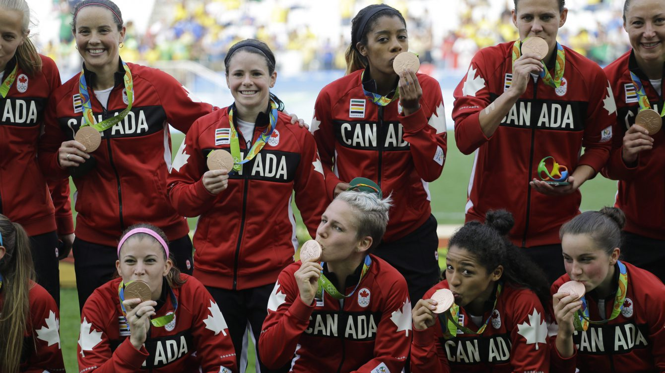 Canada team poses for photos after winning the bronze medal in the women's Olympic football tournament between Brazil and Canada at the Arena Corinthians stadium in Sao Paulo, Friday Aug. 19, 2016. (AP Photo/Nelson Antoine)