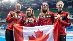 (L-R), Chantal Van Landeghem, Sandrine Mainville, Penny Oleksiak and Taylor Ruck celebrate their Olympic bronze medal in women's 4x100m freestyle relay on August 6, 2016.