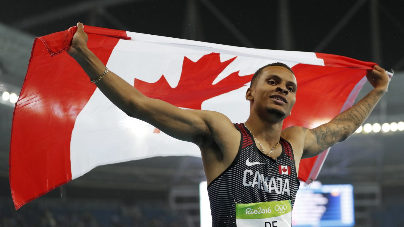 Canada's Andre De Grasse celebrates with his nation's flag after earning a silver medal in the men's 200m final in Rio on August 18, 2016. (photo/ Stephen Hosier)