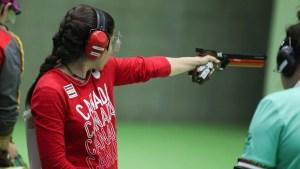 Lynda Kiejko holds her pistol at arms length to shoot