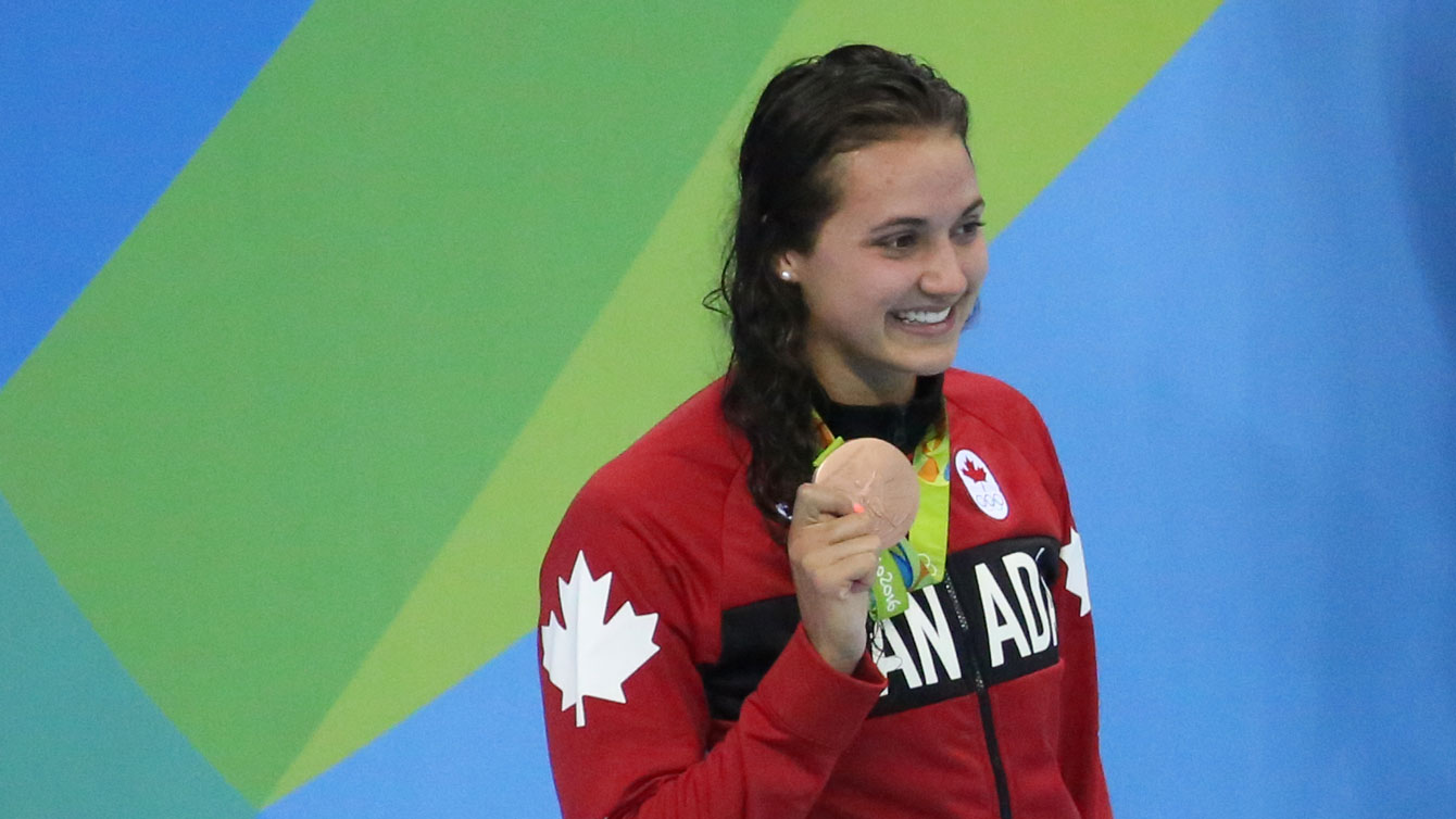 Kylie Masse holds up her Olympic bronze medal at Rio 2016 after the 100m backstroke on August 8, 2016.