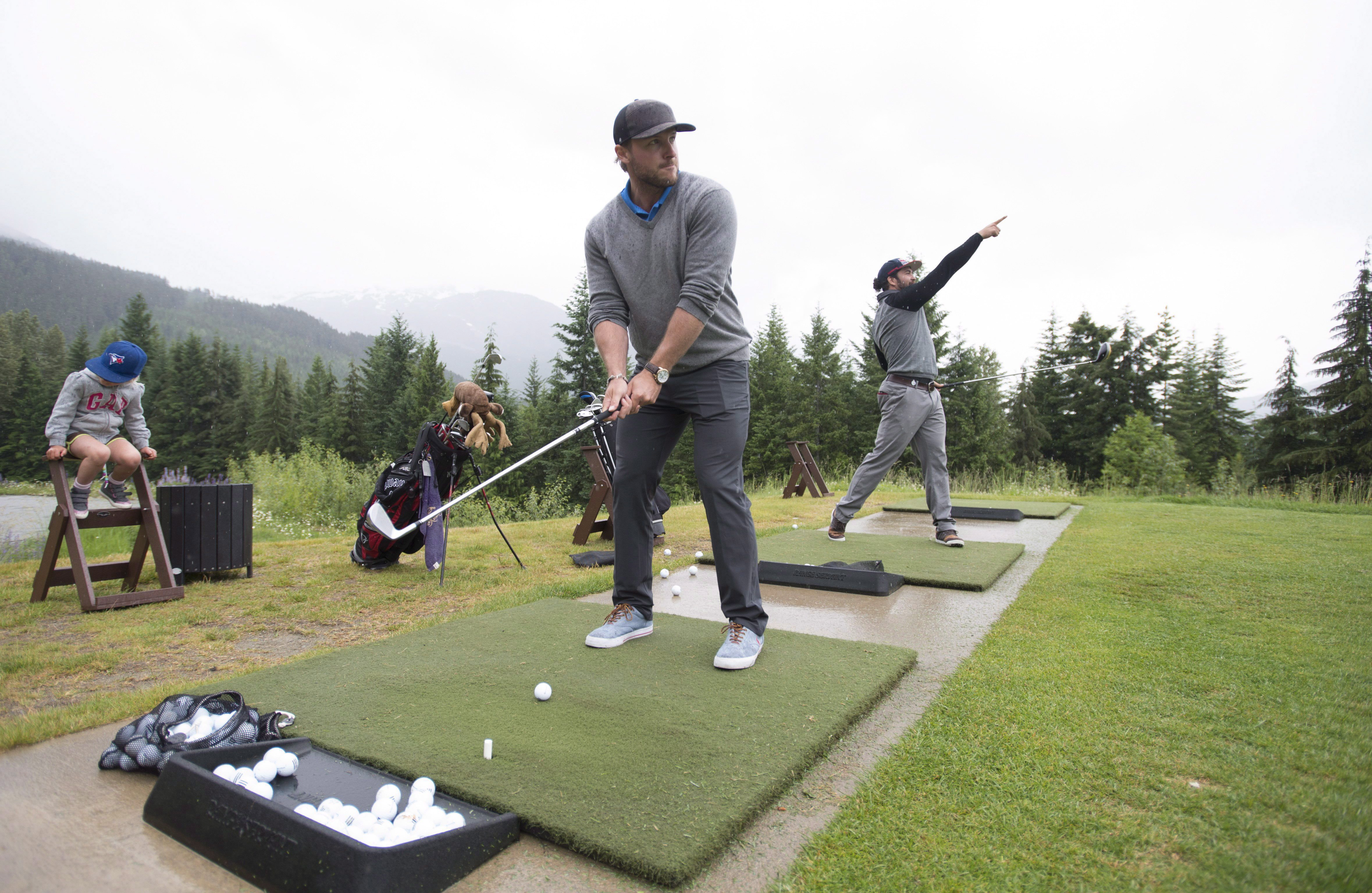 Bobsled athletes Chris Spring, right, and Justin Kripps hit shots at the Fairmont driving range in Whistler, B.C., Wednesday, June, 8, 2016. Spring and Kripps have taken up golf this summer as part of their training program, with a goal of sharpening focus and improving mental toughness. THE CANADIAN PRESS/Jonathan Hayward