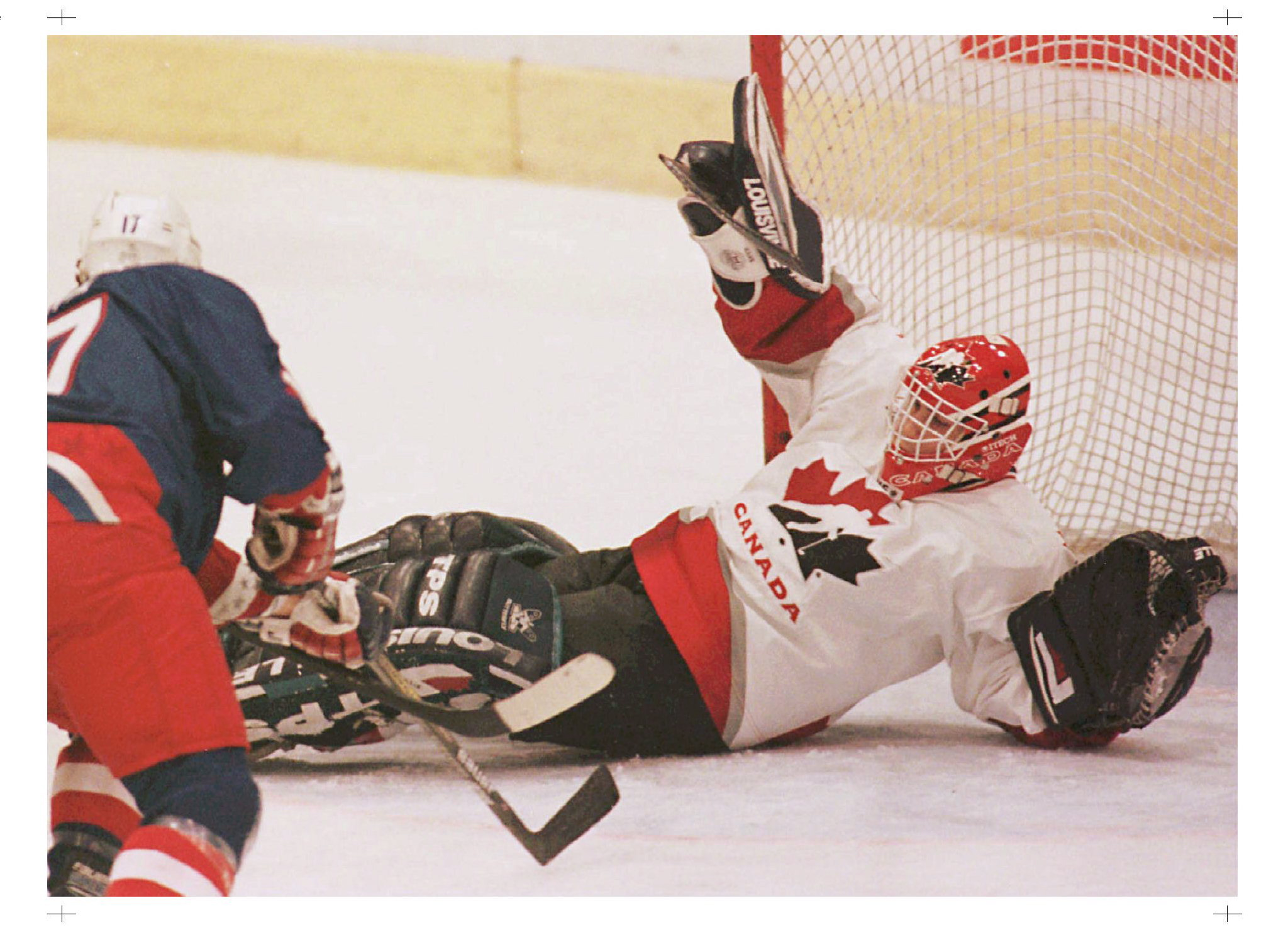 Team Canada goaltender Marc Denis makes the save off USA's Joseph Corvo during first period action at the World Junior Hockey Championships in Geneva Saturday. Canada beat the U.S. 2-0 to win their fifth consecutive title.(CP PHOTO/Ryan Remiorz)