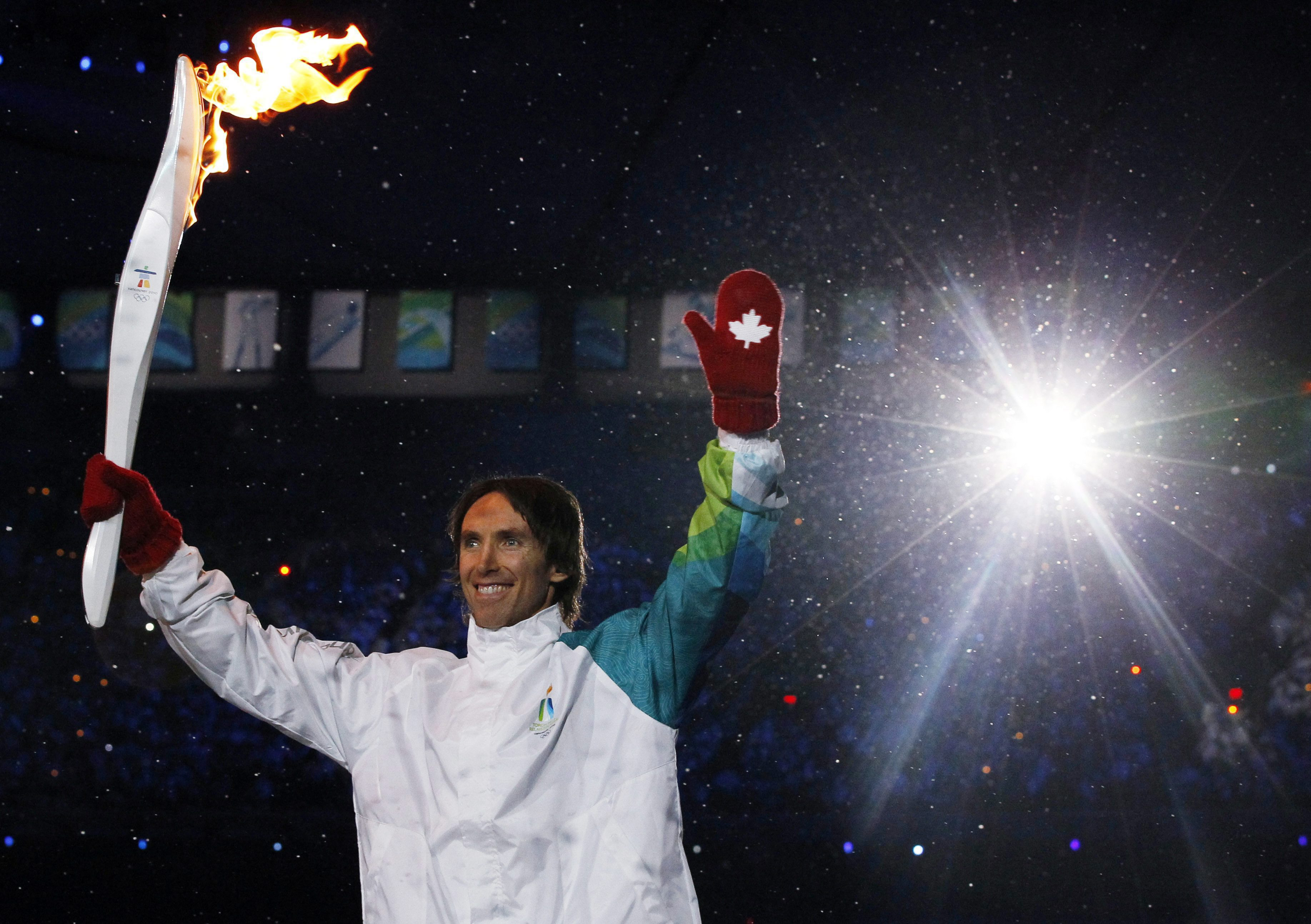 Torchbearer smiles as he waves to the crowd