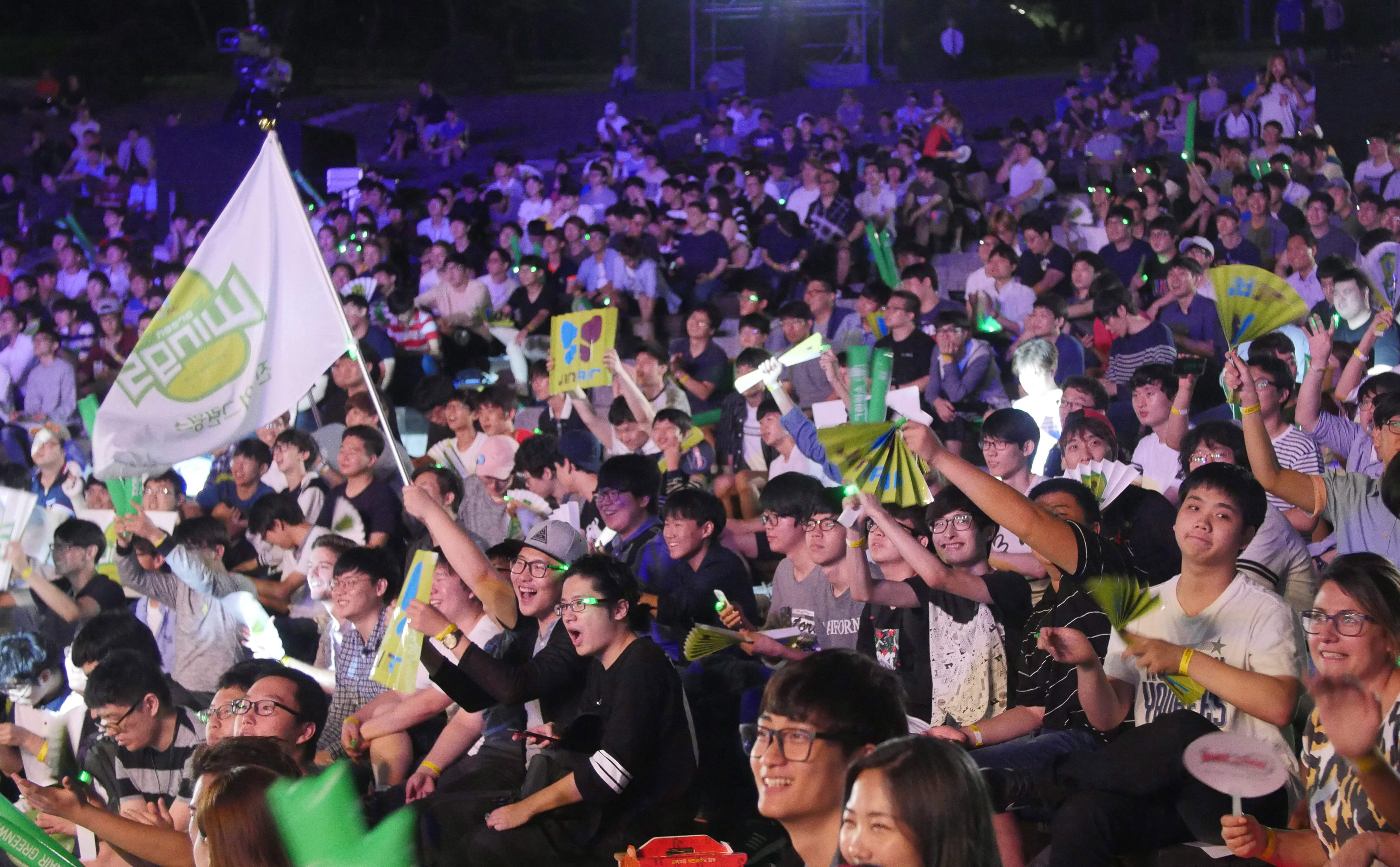 In this Sept. 3, 2016, photo, fans of Jin Air Green Wings celebrate the victory together after the 2016 SK Telecom StarCraft final match between KT Rolster and Jin Air Green Wings at Children's Grand park in Seoul, South Korea. South Korea has the biggest e-Sports industry in the world with professional leagues and broadcasting channels. (AP Photo/Jungho Choi)
