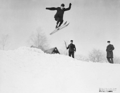 Ski jumping in the 1900s. Black and white image of a male athlete jumping over a hill.