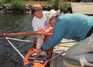 Rower Silken Laumann receives assistance adjusting her leg brace in Victoria Wednesday, June 17, 1992 from friend Peter Smith. Laumann has returned to rowing to help recover from injuries received last month at a meet in Germany. (CP PHOTO/Bruce Stotesbury)