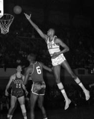 Wilt Chamberlain shoots over Boston defenders in Philadelphia, 1960. (AP Photo/files)