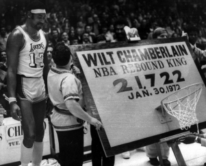 Wilt Chamberlain stands beside a backboard and hoop trophy after being named the all-time leading rebounder in NBA history, in Los Angeles, 1972. ( AP Photo / file )
