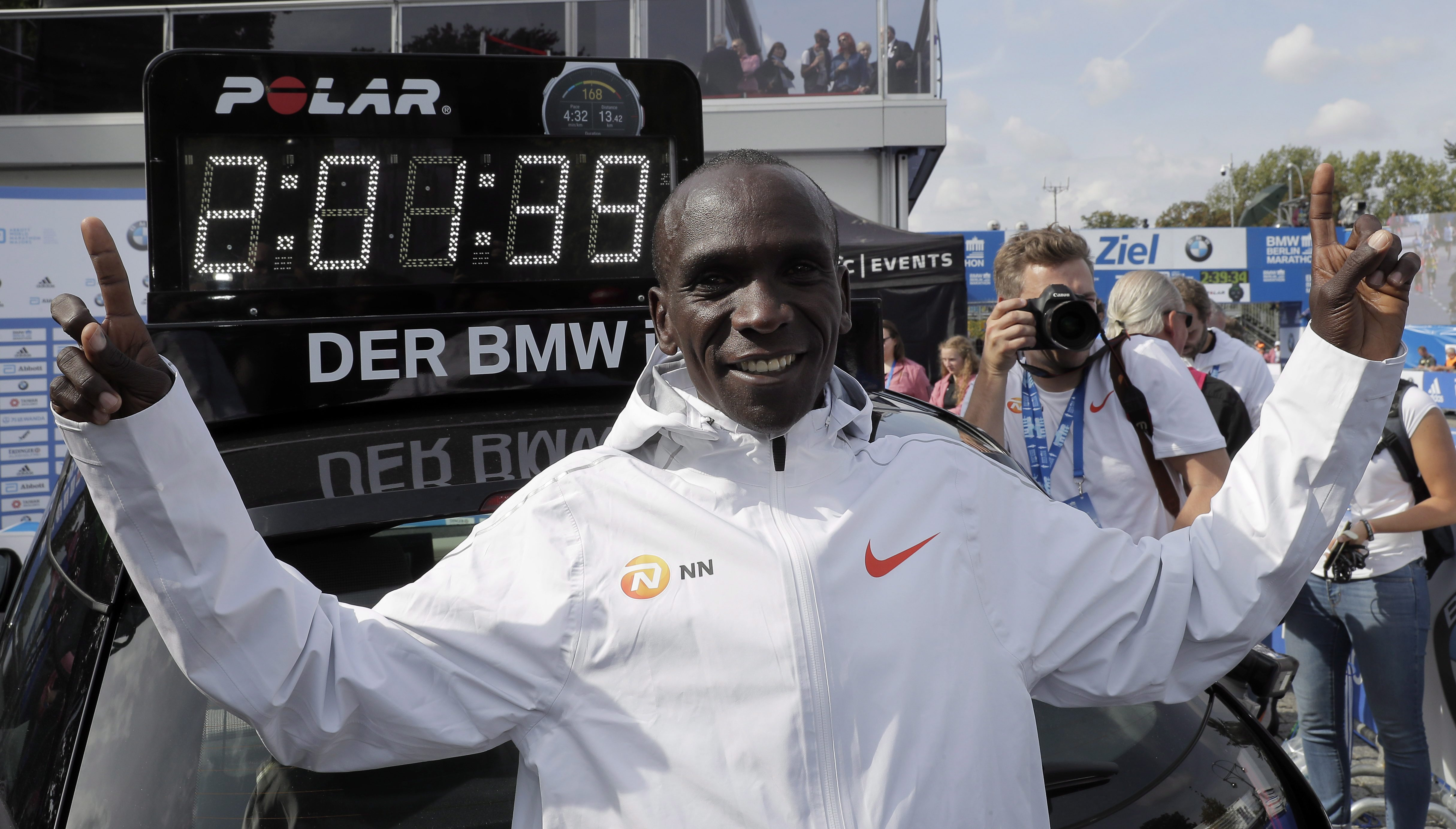 Eliud Kipchoge in front of the clock showing his world record time