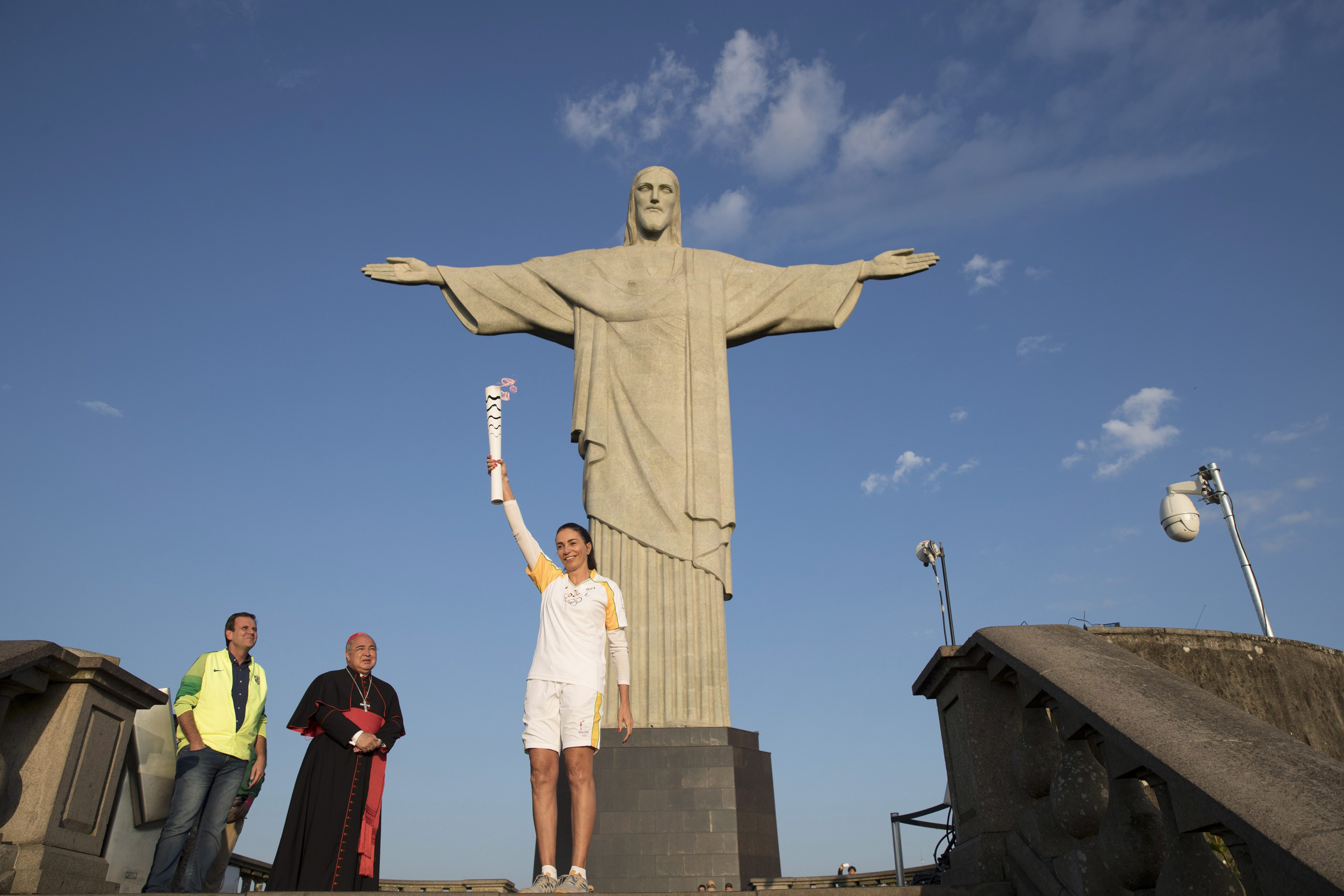 Brazil's Isabel Barroso Salgado carries the Olympic torch in front of the Christ the Redeemer statue on its way for the opening ceremony of Rio's 2016 Summer Olympics in Rio de Janeiro, Brazil, Friday, Aug. 5, 2016.