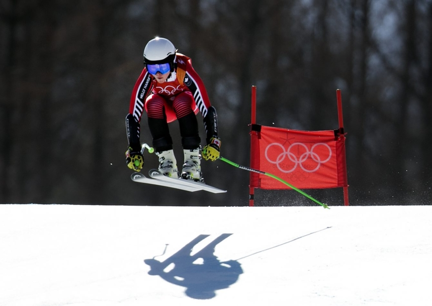 Alpine skier and her shadow going over a jump
