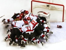 Canadian players pile on one another as the game ends in their victory