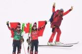 Gold medalist Kelsey Serwa, right, and silver medalist Brittany Phelan both of Canada celebrate as a skier passes by following the women's ski cross final at the Phoenix Snow Park at the 2018 Winter Olympic Games in Pyeongchang, South Korea, Friday, Feb. 23, 2018. THE CANADIAN PRESS/Jonathan Hayward
