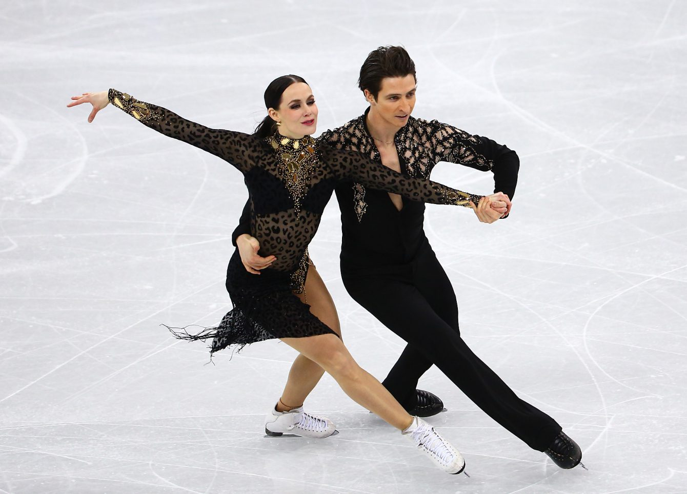 Tessa Virtue and Scott Moir in competition at the PyeongChang Games. Both are dressed in all black outfits.