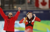 Gold medallist Canada's Christine Nesbitt, right, and her coach react as she waits for the outcome of the last race during the women's 1000 meters race at the Richmond Olympic Oval at the Vancouver 2010 Olympics in Vancouver, British Columbia, Thursday, Feb. 18, 2010. (AP Photo/Kevin Frayer)