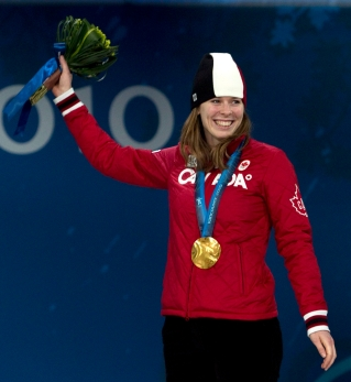 Canadian speedskater Christine Nesbitt, from London, Ont., stands on the podium after receiving her gold medal for the women's long-track 1,000m competition during the medal ceremonies in Vancouver, BC Thursday Feb. 18, 2010. THE CANADIAN PRESS/Adrian Wyld