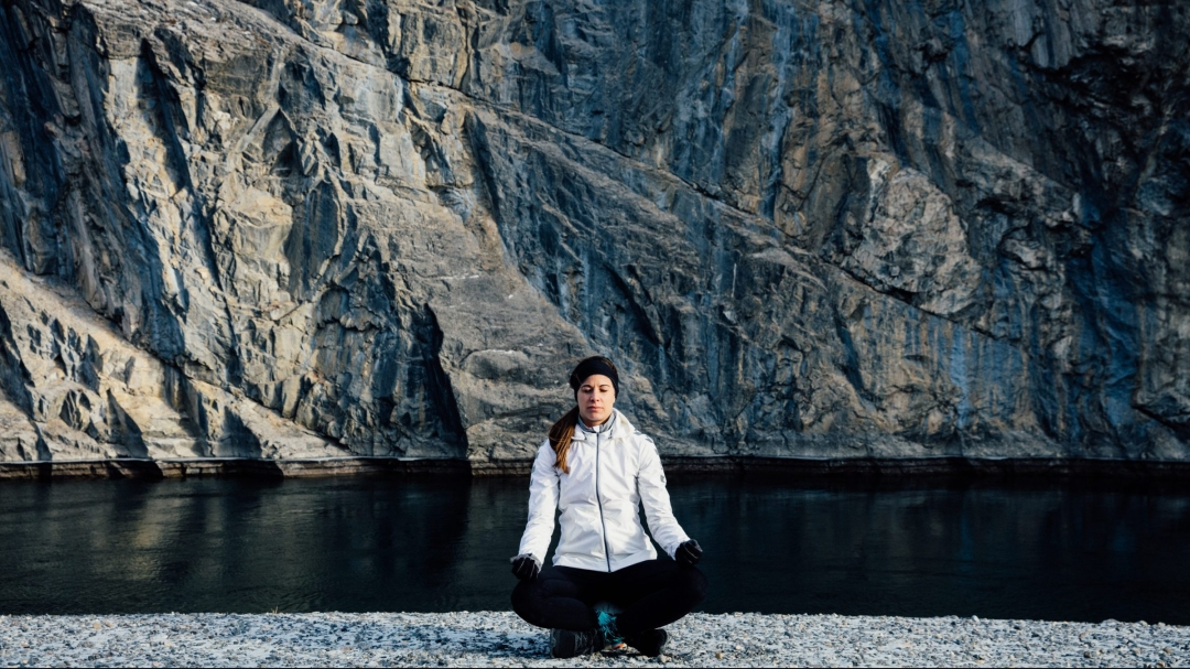 Steph Labbe meditates by a lake and mountains