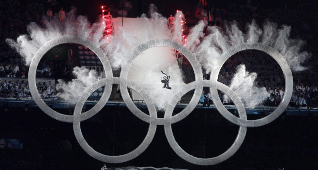 A snowboarder sailing through the Olympic rings during the opening ceremonies of Vancouver 2010