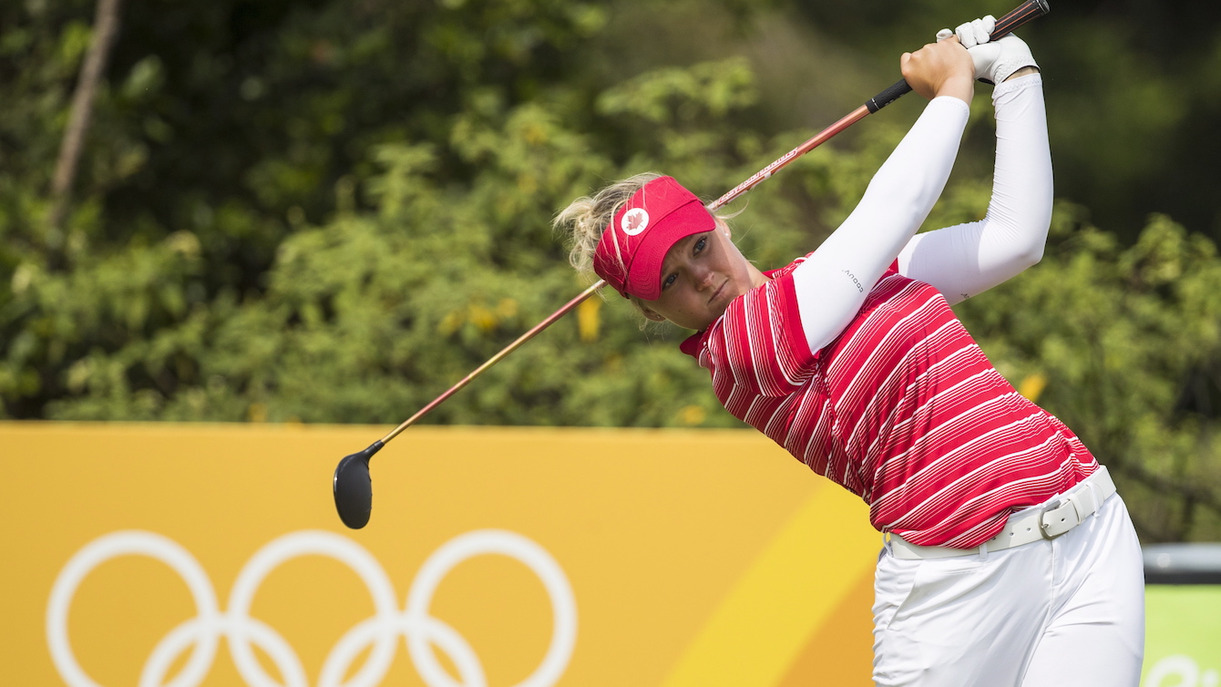 Brooke Henderson tees off in front of Olympic rings