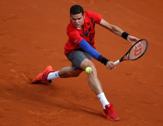 Canada's Milos Raonic backhands to Serbia's Novak Djokovic during their quarterfinal match of the French Open tennis tournament at the Roland Garros stadium, in Paris, France, Tuesday, June 3, 2014. (AP Photo/Michel Euler)
