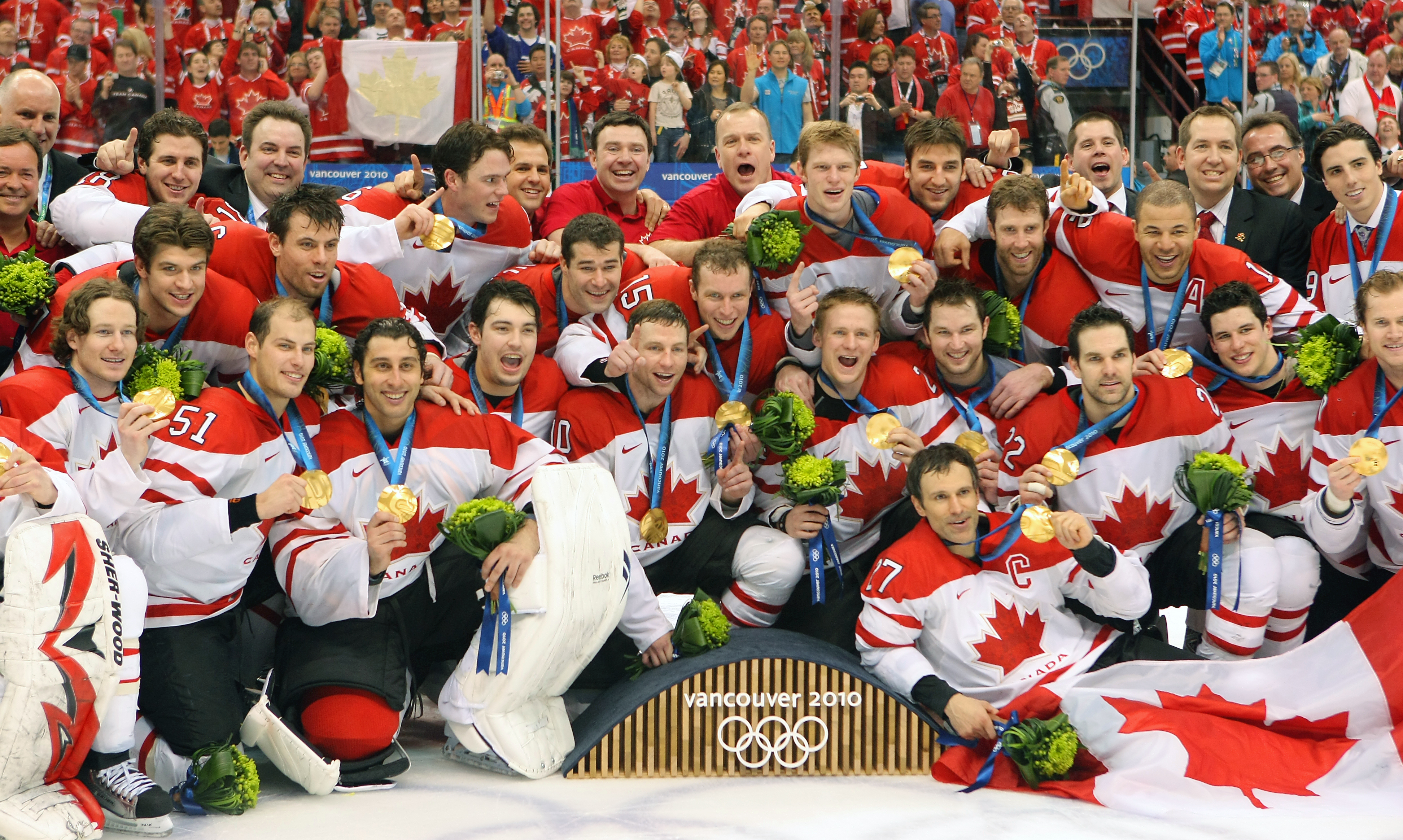 The men's hockey team pose with their gold medals at Vancouver 2010