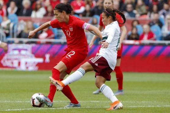 Christine Sinclair battles for the ball