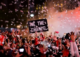 Fan celebrate in Jurassic Park as confetti falls