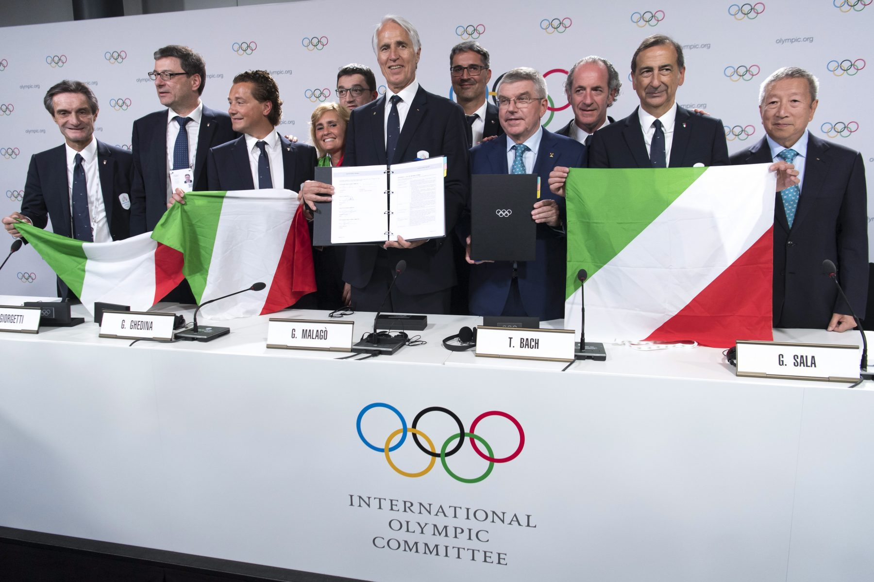 group of people in suits holding italian flags at IOC press conference