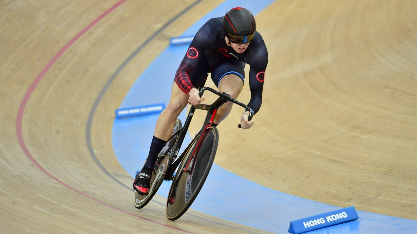 Nick Wammes making a turn on the track. He is in a black and red cycling suit.
