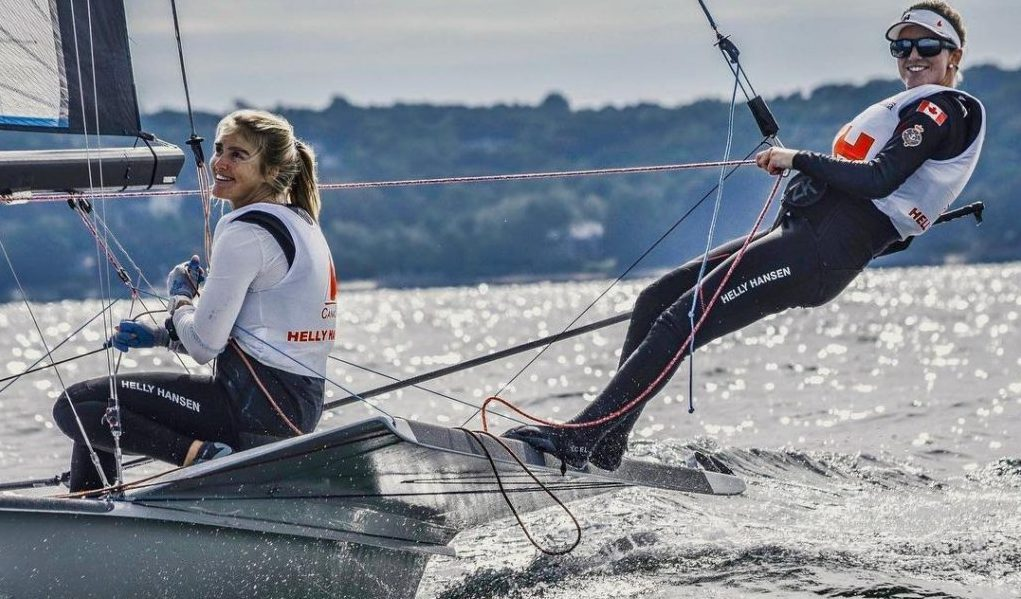 Ali Ten Hove and Mariah Millen smile while sailing.