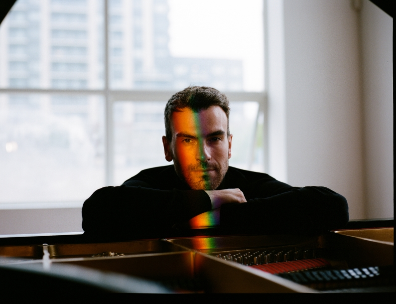 Man sitting at piano with rainbow light on face