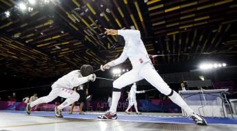 Joel Riker-Fox, left, of Canada competes in menÕs fencing