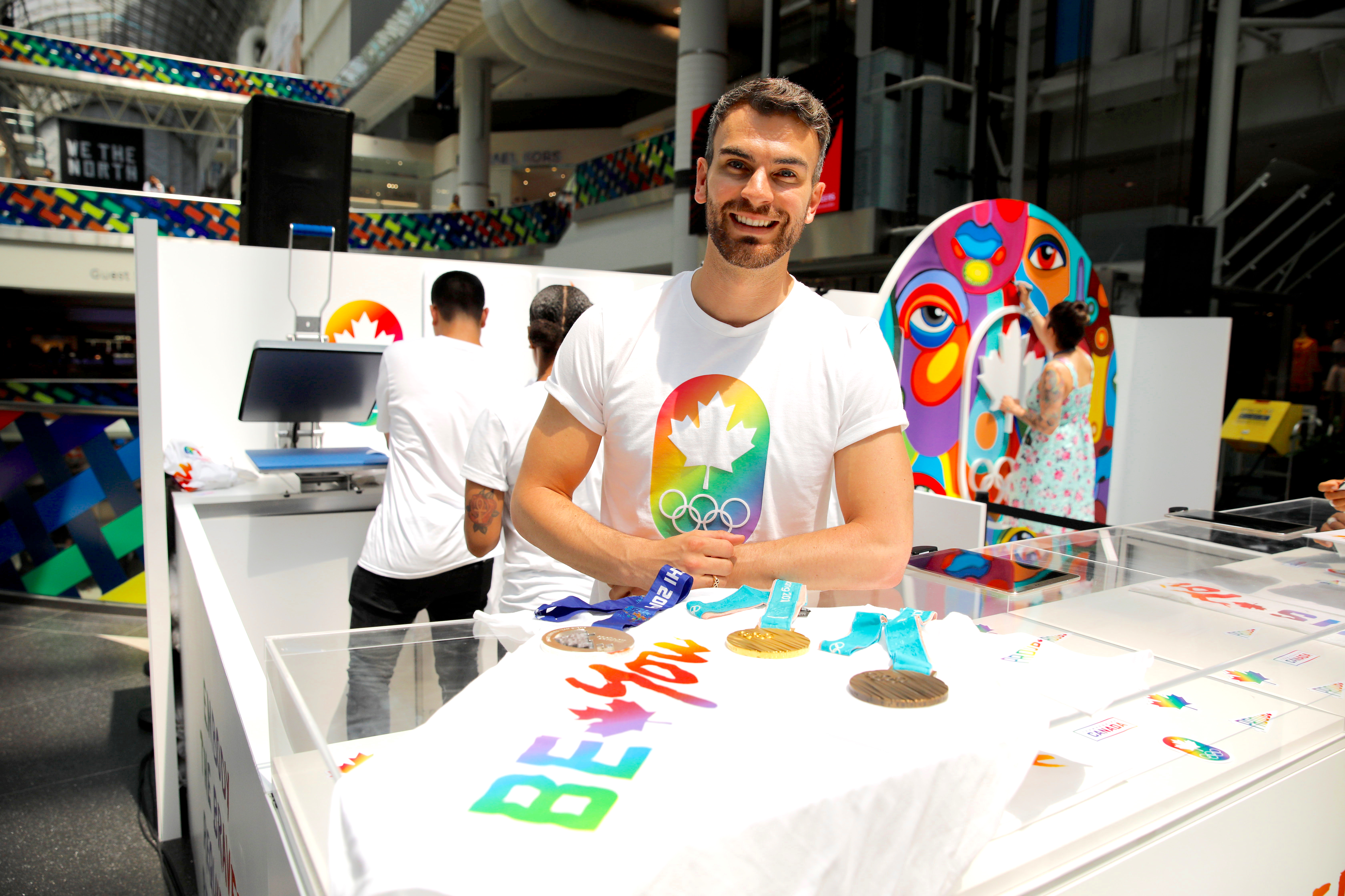 Eric Radford poses in front of the 2019 Be You pop-up with his three Olympic medals.