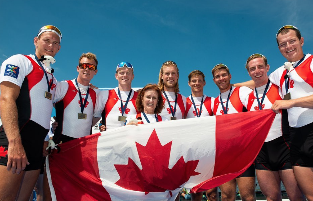 Team Canada standing in front of flag with bronze medals.