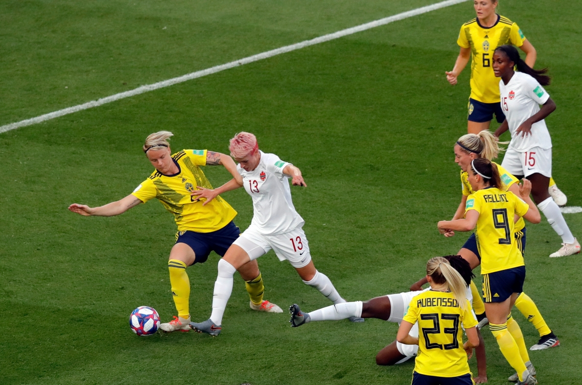 Sweden's Nilla Fischer vies for the ball with Canada's Sophie Schmidt