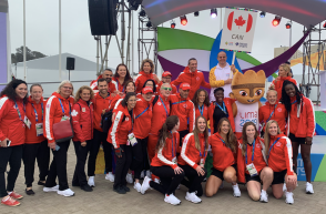 Group shot of athletes being welcomed in the village