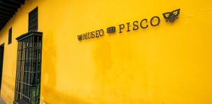 Yellow wall with Pisco liquor museum sign