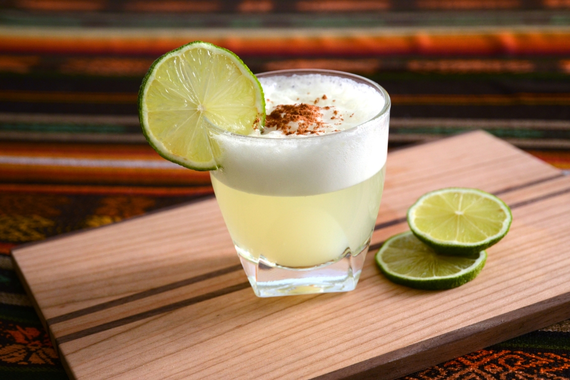A photo of a pisco sour in Peru, garnished with a lime.