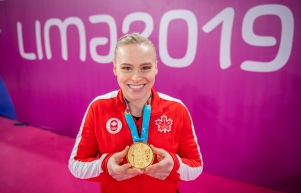 Athlete poses with her gold medal in front of Lima 2019 sign