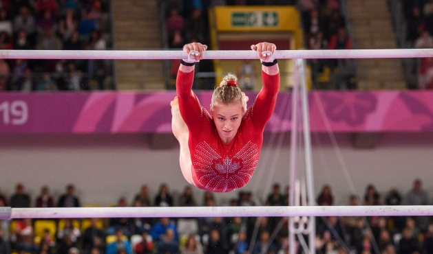 Gymnast swings on the uneven bars