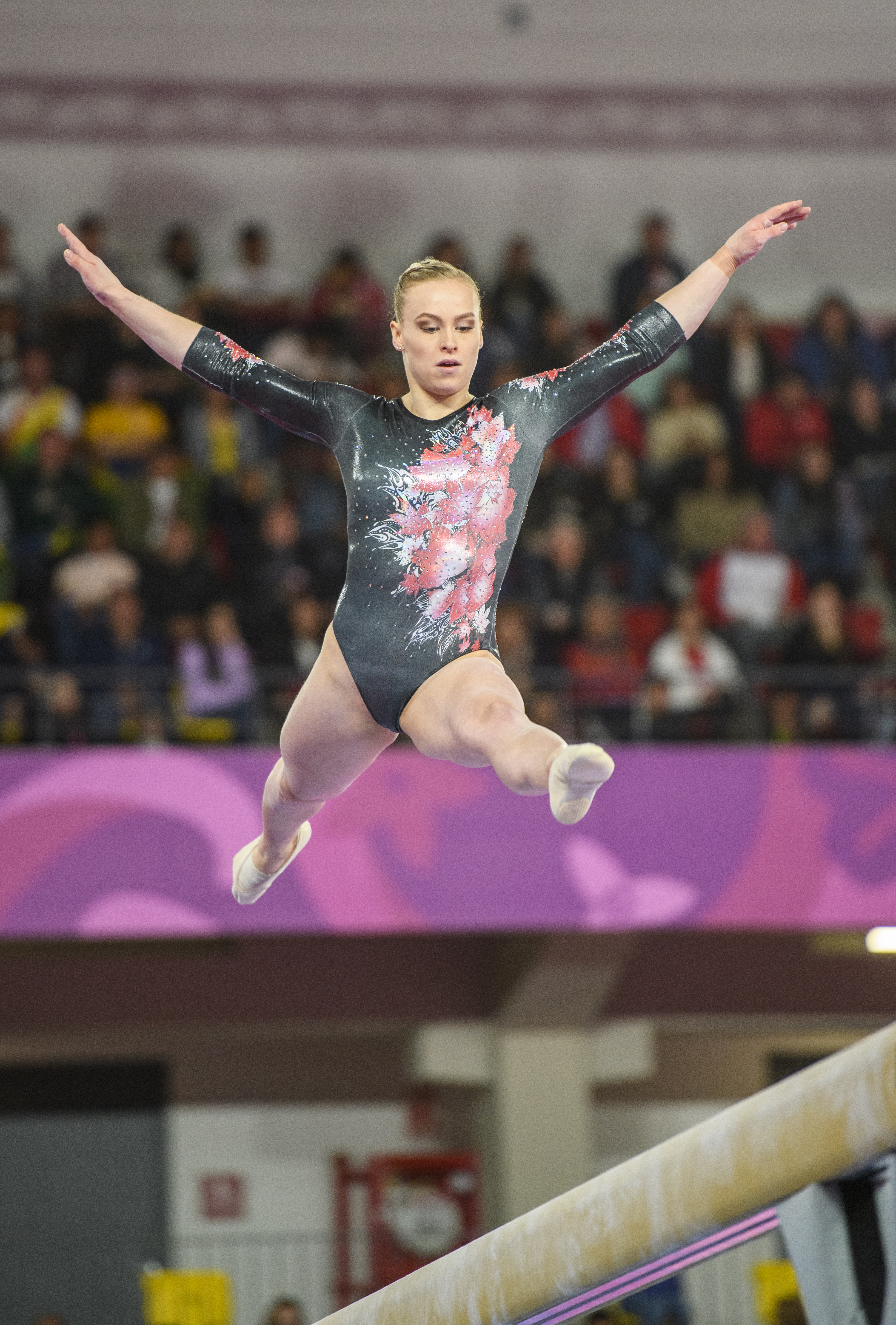 Gymnast does a split leap on the beam