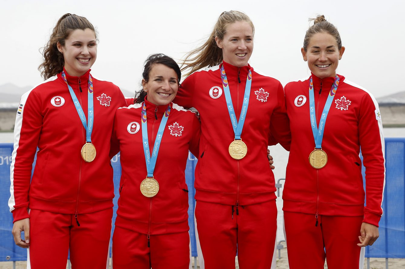 Athletes stand on the podium wearing gold medals.